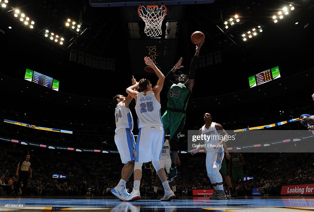 Gerald Wallace #45 of the Boston Celtics with a shot over Timofey Mozgov #25 and Evan Fournier #94 of the Denver Nuggets The Boston Celtics versus the Denver Nuggets on January 7, 2014 at the Pepsi Center in Denver, Colorado.
