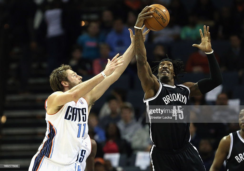 Gerald Wallace #45 of the Brooklyn Nets and Josh McRoberts #11 of the Charlotte Bobcats battle for a loose ball during their game at Time Warner Cable Arena on March 6, 2013 in Charlotte, North Carolina.