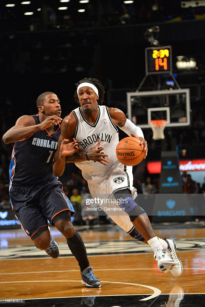 Gerald Wallace #45 of the Brooklyn Nets dribbles around Ramon Sessions #7 of the Charlotte Bobcats during the game at the Barclays Center on December 28, 2012 in Brooklyn, New York.