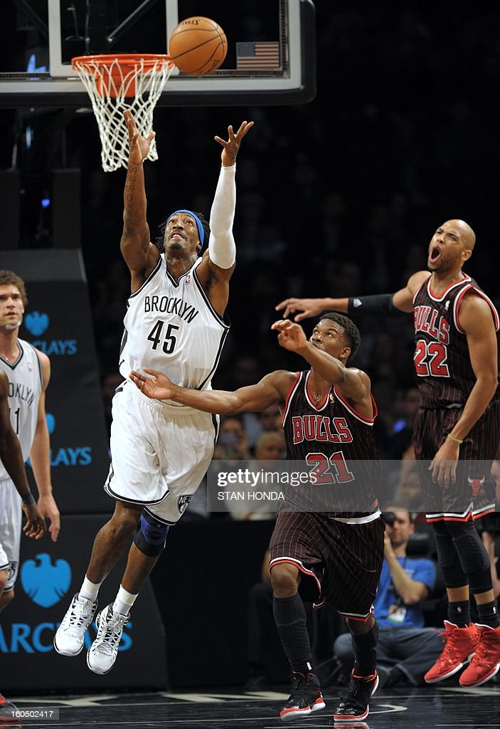 Gerald Wallace (L) of the Brooklyn Nets fights for a rebound against Jimmy Butler (C) of the Chicago Bulls as Taj Gibson (R) reacts during game at the Barclay Center February 1, 2013 in the Brooklyn borough of New York. The Nets won, 93-89. AFP PHOTO/Stan HONDA