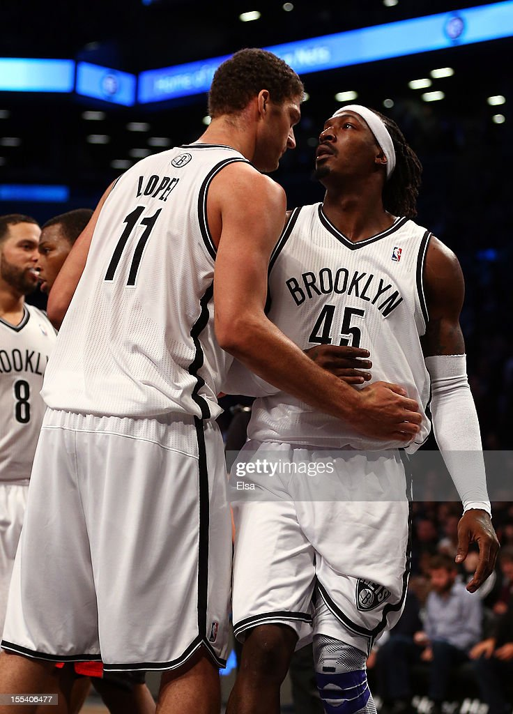 <a gi-track='captionPersonalityLinkClicked' href=/galleries/search?phrase=Gerald+Wallace&family=editorial&specificpeople=202117 ng-click='$event.stopPropagation()'>Gerald Wallace</a> #45 of the Brooklyn Nets is helped up by <a gi-track='captionPersonalityLinkClicked' href=/galleries/search?phrase=Brook+Lopez&family=editorial&specificpeople=3847328 ng-click='$event.stopPropagation()'>Brook Lopez</a> #11 after Wallace was fouled in the fourth quarter against the Toronto Raptors on November 3, 2012 in the Brooklyn borough of New York City. The Brooklyn Nets defeated the Toronto Raptors 107-100.