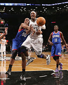 Gerald Wallace of the Brooklyn Nets is tripped up in the game against the Philadelphia 76ers at Barclays Center on December 23 2012 in the Brooklyn...
