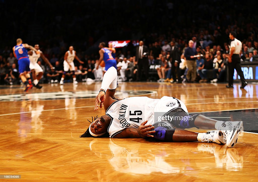 Gerald Wallace #45 of the Brooklyn Nets lies on the court in pain after hurting his knee against the New York Knicks during their game at the Barclays Center on December 11, 2012 in the Brooklyn borough of New York City.