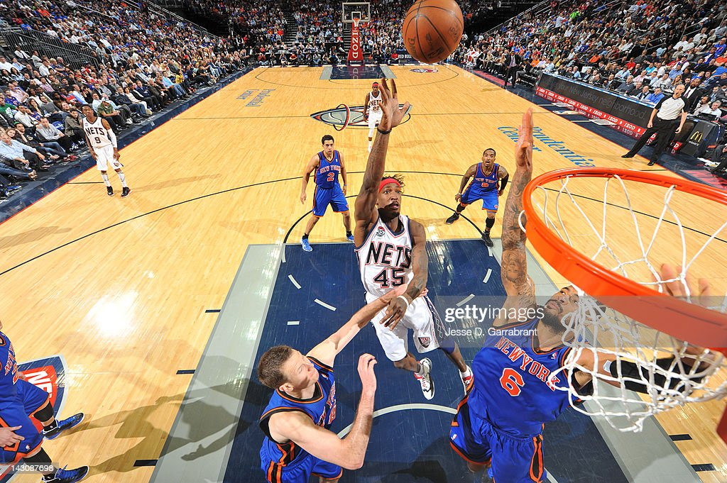 <a gi-track='captionPersonalityLinkClicked' href=/galleries/search?phrase=Gerald+Wallace&family=editorial&specificpeople=202117 ng-click='$event.stopPropagation()'>Gerald Wallace</a> #45 of the New Jersey Nets shoots against <a gi-track='captionPersonalityLinkClicked' href=/galleries/search?phrase=Tyson+Chandler&family=editorial&specificpeople=202061 ng-click='$event.stopPropagation()'>Tyson Chandler</a> #6 of the New York Knicks on April 18, 2012 at the Prudential Center in Newark, New Jersey.