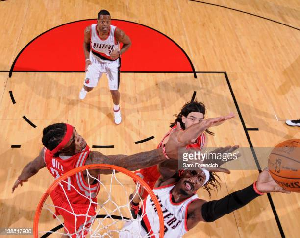 Gerald Wallace of the Portland Trail Blazers reaches for the ball against Jordan Hill and Luis Scola of the Houston Rockets as teammate Marcus Camby...