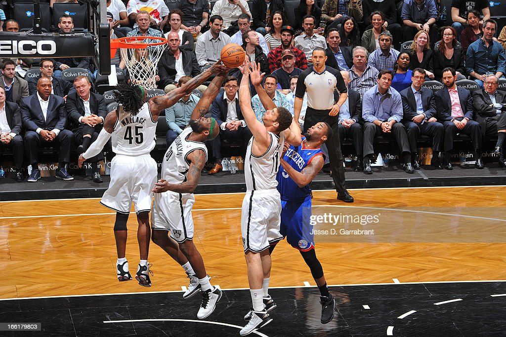 Gerald Wallace #45, Reggie Evans #30, and Brook Lopez #11 of the Brooklyn Nets reach for a rebound against Arnett Moultrie #5 of the Philadelphia 76ers on April 9, 2013 at the Barclays Center in Brooklyn, New York.
