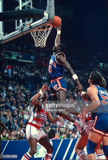 Gerald Wilkins of the New York Knicks jams the ball over Cliff Robinson of the Washington Bullets during an NBA basketball game circa 1985 at the...