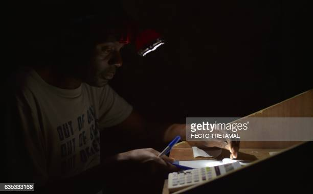 TOPSHOT Gerald works in a small stand playing the lotto in Jalousie neighborhood in the commune of Petion Ville in the Haitian capital PortauPrince...