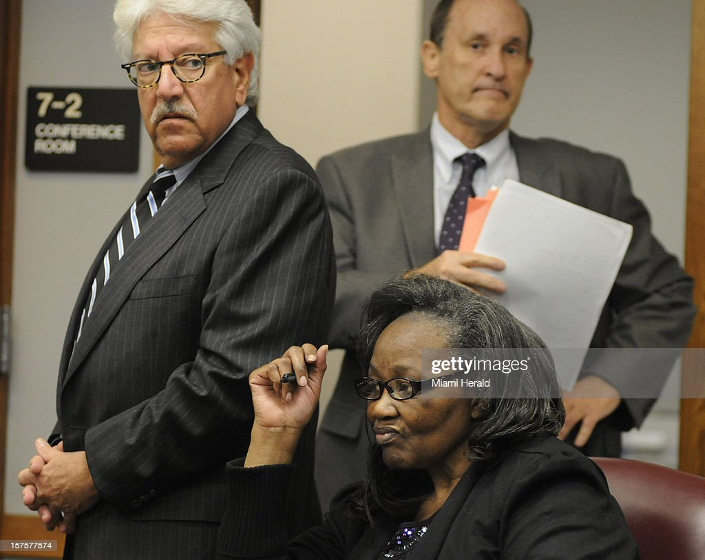 Geralyn Graham, center, sits in a courtroom with her attorneys Michael Matters, left, and Scott Sakin, right, pictured in the background, during her trial in Miami-Dade Criminal Court Tuesday, December 4, 2012, in Miami, Florida. Graham is charged with the murder of four-year-old Rilya Wilson.