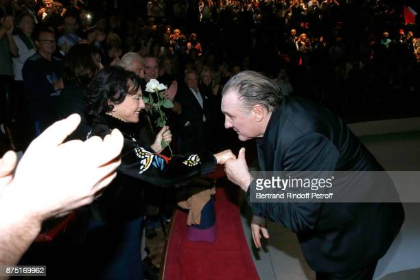 Gerard Depardieu acknowledges the applause of the audience and gives flowers to Monique Lang at the end of 'Depardieu Chante Barbara' at 'Le Cirque...