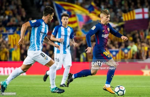 Gerard Deulofeu Lazaro of FC Barcelona is followed by Adrian Gonzalez Morales of Malaga CF during the La Liga 201718 match between FC Barcelona and...