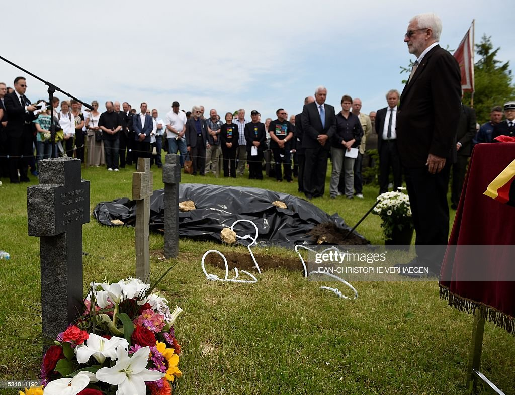 Gerard Gervaise, mayor of Haumont-Samogneux, pays his respect in front of the grave of Hans Winckelmann, a German soldier who died in WWI, during his burial at the German WWI cemetery of Romagne-sous-Montfaucon, eastern France on May 28, 2016, as part of the Verdun battle commemoration. / AFP / JEAN