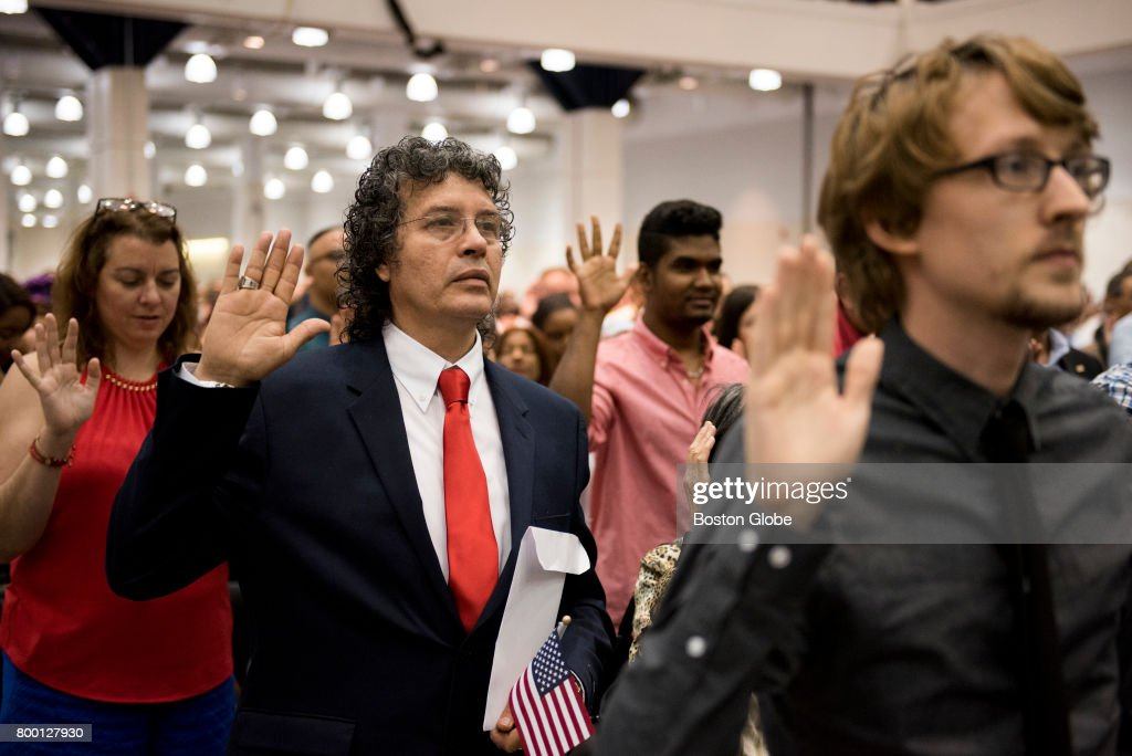 Gerard Gonzalez, center-left, raises his hand for the Oath of Allegiance to America during the U.S. Citizenship and Immigration Services naturalization proceeding at the Hynes Convention Center in Boston on Jun. 22, 2017. Over 2500 people became US citizens following this proceeding, presided over by the Honorable Joan N. Feeney, a United States Bankruptcy Judge.