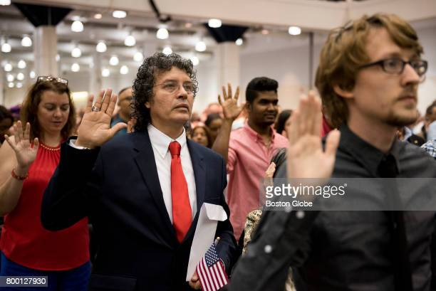 Gerard Gonzalez centerleft raises his hand for the Oath of Allegiance to America during the US Citizenship and Immigration Services naturalization...