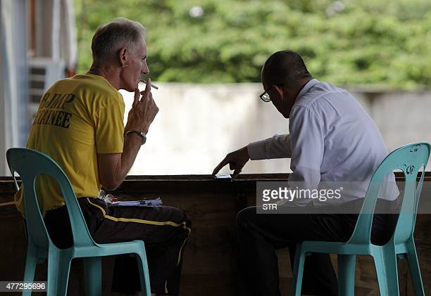 Gerard Peter Scully of Australia accused of raping and trafficking two girls in the Philippines smokes a cigarette as he confers with his lawyer...
