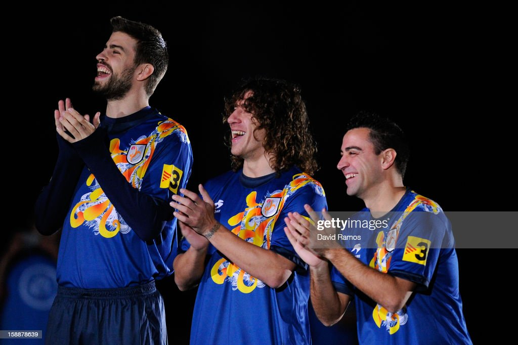 Gerard Pique, Carles Puyol and Xavi Hernandez of Catalonia smile and appluad prior to a friendly match between Catalonia and Nigeria at Cornella-El Prat Stadium on January 2, 2013 in Barcelona, Spain.