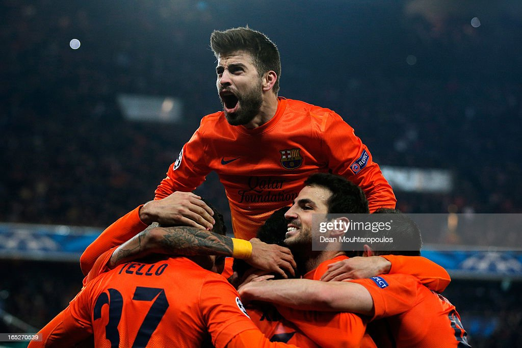 Gerard Pique jumps on Xavi of Barcelona as they celebrate with team mates after scoring a penalty for the teams second goal during the UEFA Champions League Quarter Final match between Paris Saint-Germain and Barcelona FCB at Parc des Princes on April 2, 2013 in Paris, France.