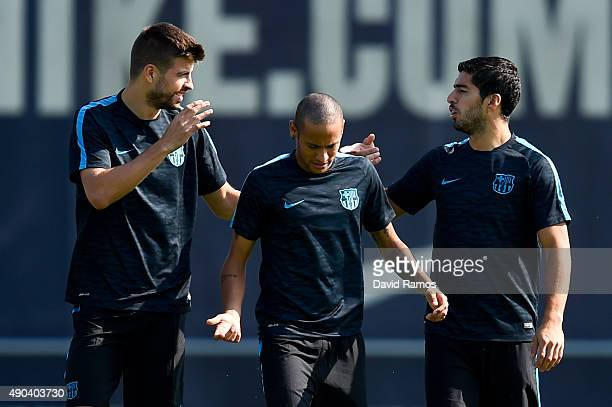 Gerard Pique Neymar and Luis Suarez of FC Barcelona talk during a training session ahead of their UEFA Champions League Group E match against Bayern...