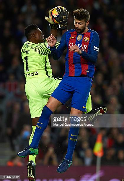 Gerard Pique of Barcelona competes for the ball with Carlos Kameni of Malaga during the La Liga match between FC Barcelona and Malaga CF at Camp Nou...