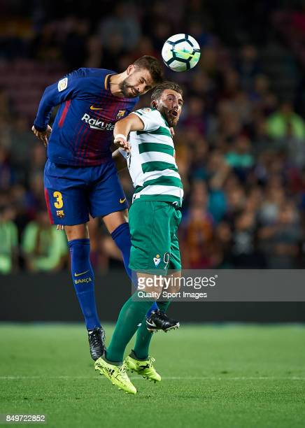 Gerard Pique of Barcelona competes for the ball with Sergi Enrich of Eibar during the La Liga match between Barcelona and Eibar at Camp Nou on...
