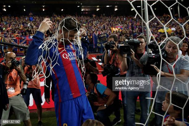 Gerard Pique of Barcelona cuts down the goal net as Barcelona players celebrate after the Copa Del Rey Final between FC Barcelona and Deportivo...