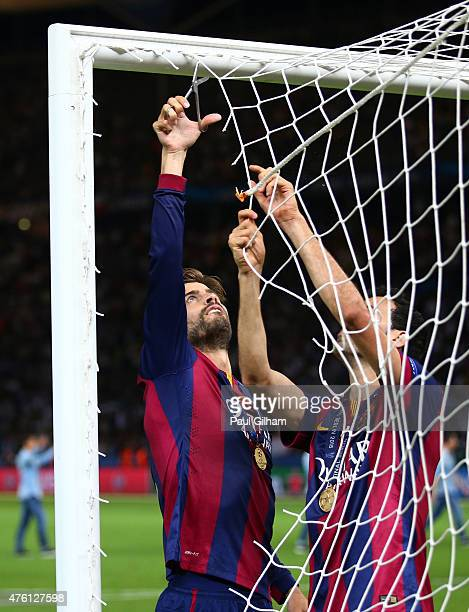 Gerard Pique of Barcelona cuts the net as he celebrates victory after the UEFA Champions League Final between Juventus and FC Barcelona at...