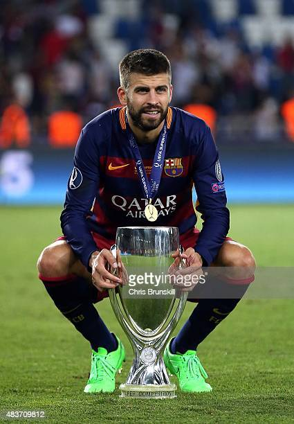 Gerard Pique of Barcelona poses with the trophy following the UEFA Super Cup match between Barcelona and Sevilla FC at Dinamo Stadium on August 11...