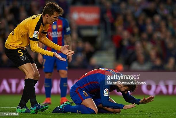 Gerard Pique of Barcelona reacts on the pitch next to Diego Llorente of Malaga during the La Liga match between FC Barcelona and Malaga CF at Camp...
