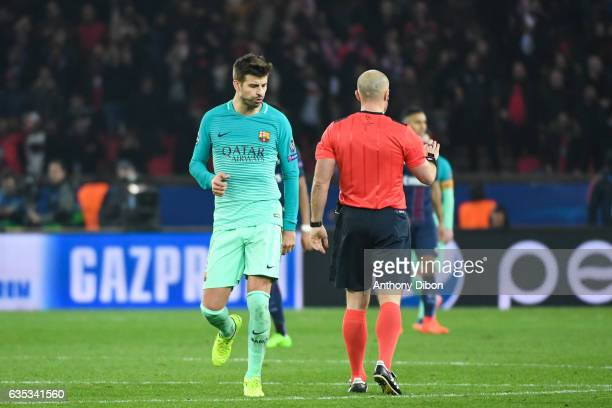 Gerard Pique of Barcelona talks with referee Szymon Marciniak during the Champions league match between Paris Saint Germain and FC Barcelona at Parc...