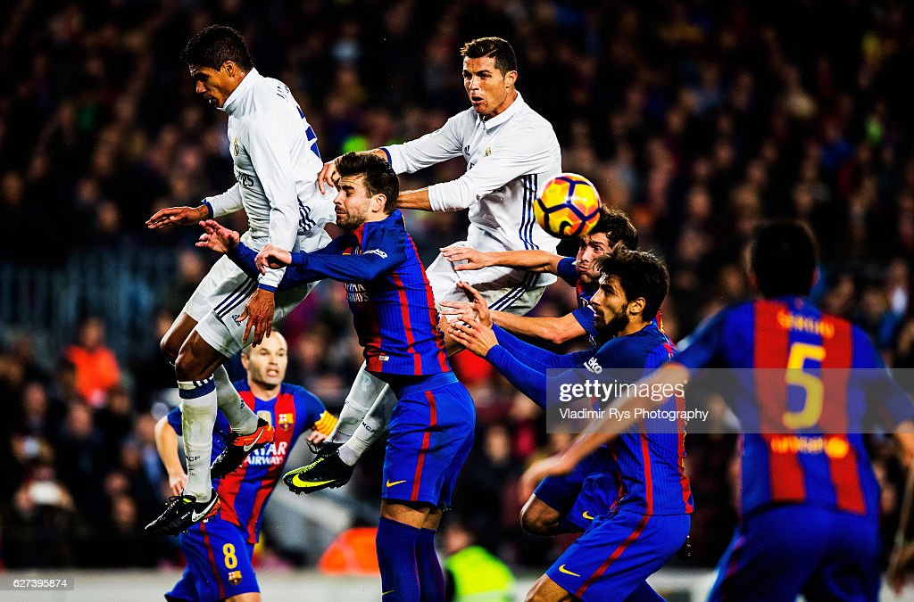 Gerard Pique of Barcelona vies for a header with Rafael Varane and Cristiano Ronaldo of Real Madrid during the La Liga match between FC Barcelona and...