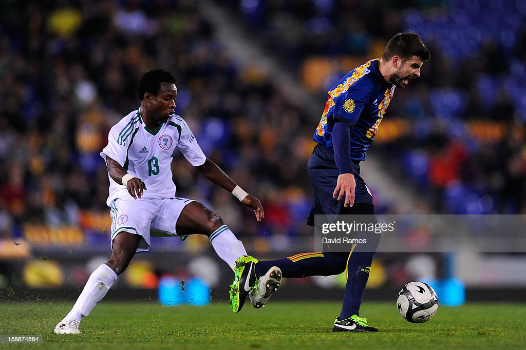 Gerard Pique (R) of Catalonia duels for the ball with Emenike Emmanuel of Nigeria during a friendly match between Catalonia and Nigeria at Cornella-El Prat Stadium on January 2, 2013 in Barcelona, Spain.