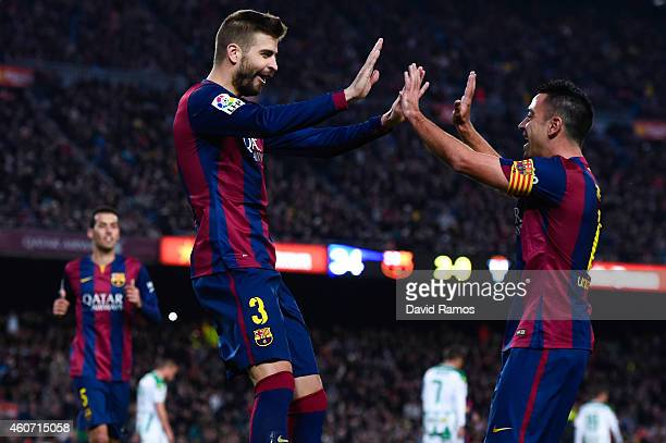 Gerard Pique of FC Barcelona celebrates with his teammate Xavi Hernandez of FC Barcelona after scoring his team's third goal during the La Liga match...
