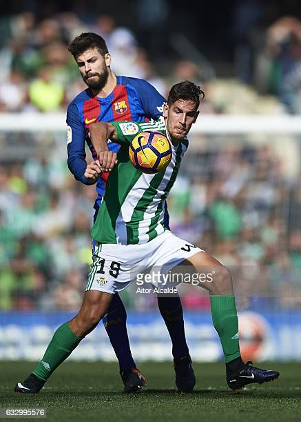 Gerard Pique of FC Barcelona competes for the ball with Roman Zozulya of Real Betis Balompie during La Liga match between Real Betis Balompie and FC...
