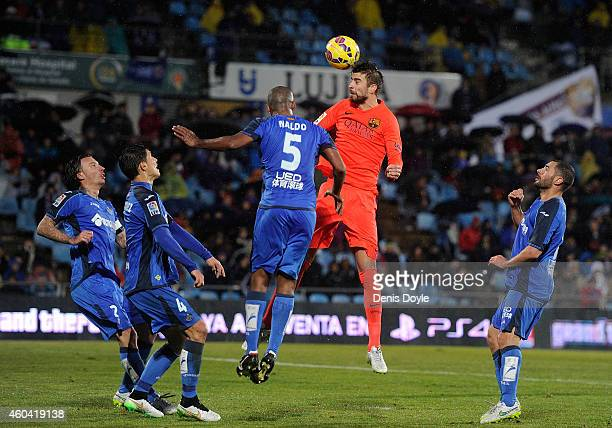 Gerard Pique of FC Barcelona heads the ball beside Edinaldo 'Naldo' Pereira da Silva of Getafe CF during the La Liga match between Getafe CF and FC...