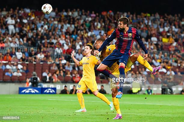 Gerard Pique of FC Barcelona heads the ball towards goal under a challenge by Joao Guilherme of APOEL FC during the UEFA Champions League Group F...
