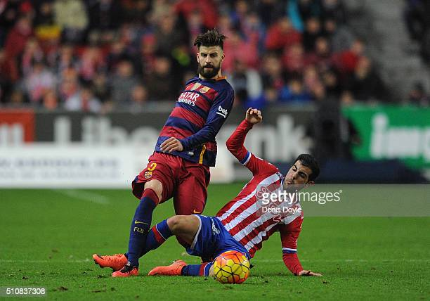 Gerard Pique of FC Barcelona is tackled by Carlos Castro of Sporting Gijon during the La Liga match between Sporting Gijon and FC Barcelona at...