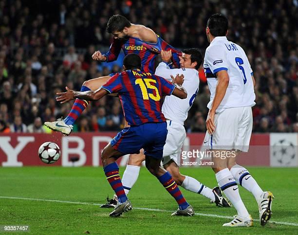 Gerard Pique of FC Barcelona scores his side's opening goal past Thiago Motta of Inter Milan as Seydou Keita of FC Barcelona and Lucio of Inter Milan...