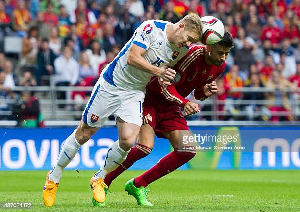 Gerard Pique of Spain duels for the ball with Tomas Hubocan of Slovakia during the Spain v Slovakia EURO 2016 Qualifier at Carlos Tartiere on...