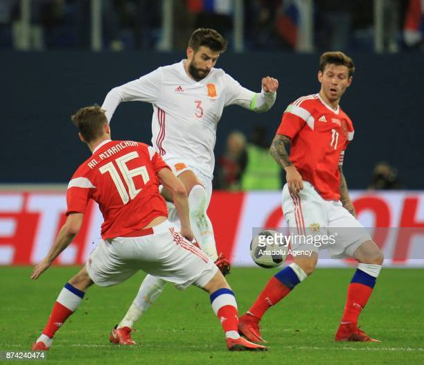 Gerard Pique of Spain in action against Fedor Smolov and Anton Miranchuk of Russia during an international friendly football match between Russia and...