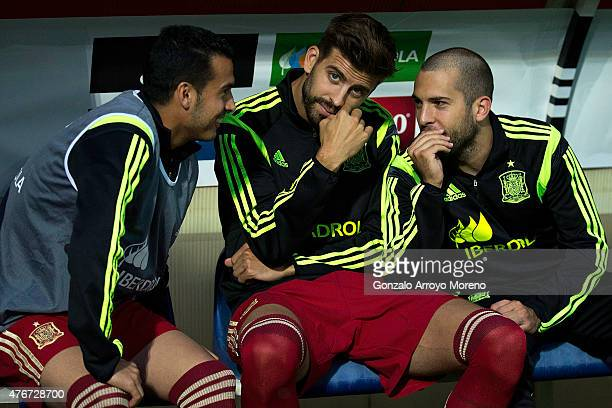 Gerard Pique of Spain looks on sitted on the bench surrounded by teammates Jordi Alba and Pedro Rodriguez Ledesma during the international friendly...