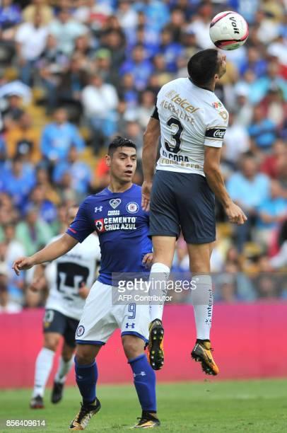 Gerardo Alcoba of Pumas jumps for the ball with Felipe Mora of Cruz Azul during their Mexican Apertura tournament football match at La Corregidora...