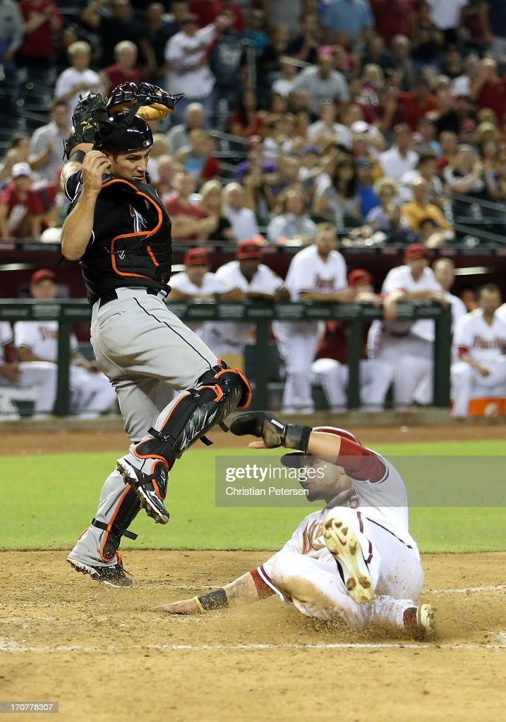 <a gi-track='captionPersonalityLinkClicked' href=/galleries/search?phrase=Gerardo+Parra&family=editorial&specificpeople=4959447 ng-click='$event.stopPropagation()'>Gerardo Parra</a> #8 of the Arizona Diamondbacks safely slides under the tag from catcher <a gi-track='captionPersonalityLinkClicked' href=/galleries/search?phrase=Jeff+Mathis&family=editorial&specificpeople=660661 ng-click='$event.stopPropagation()'>Jeff Mathis</a> #6 of the Miami Marlins to score a run during the fifth inning of the MLB game at Chase Field on June 17, 2013 in Phoenix, Arizona.