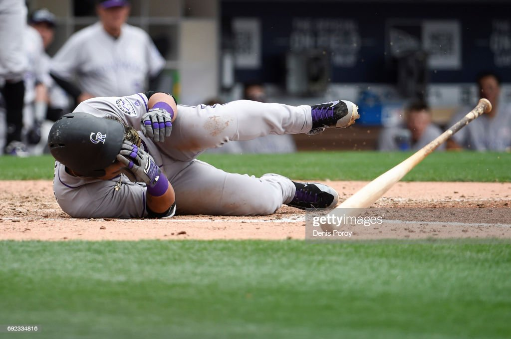 Gerardo Parra #8 of the Colorado Rockies falls to the ground after being hit with a pitch during the eighth inning of a baseball game against the San Diego Padres at PETCO Park on June 4, 2017 in San Diego, California.