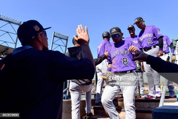 Gerardo Parra of the Colorado Rockies is greeted in the dugout by teammates during the spring training game against the Arizona Diamondbacks at Salt...