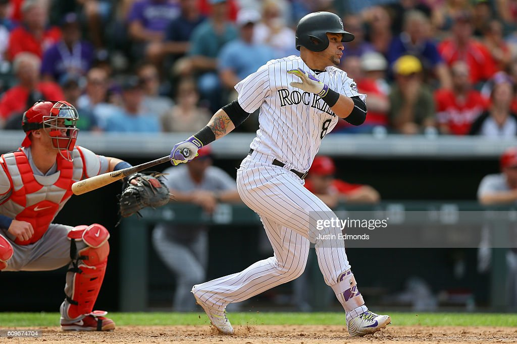Gerardo Parra #8 of the Colorado Rockies watches his RBI single during the seventh inning in front of catcher Carson Kelly #71 of the St. Louis Cardinals at Coors Field on September 21, 2016 in Denver, Colorado.