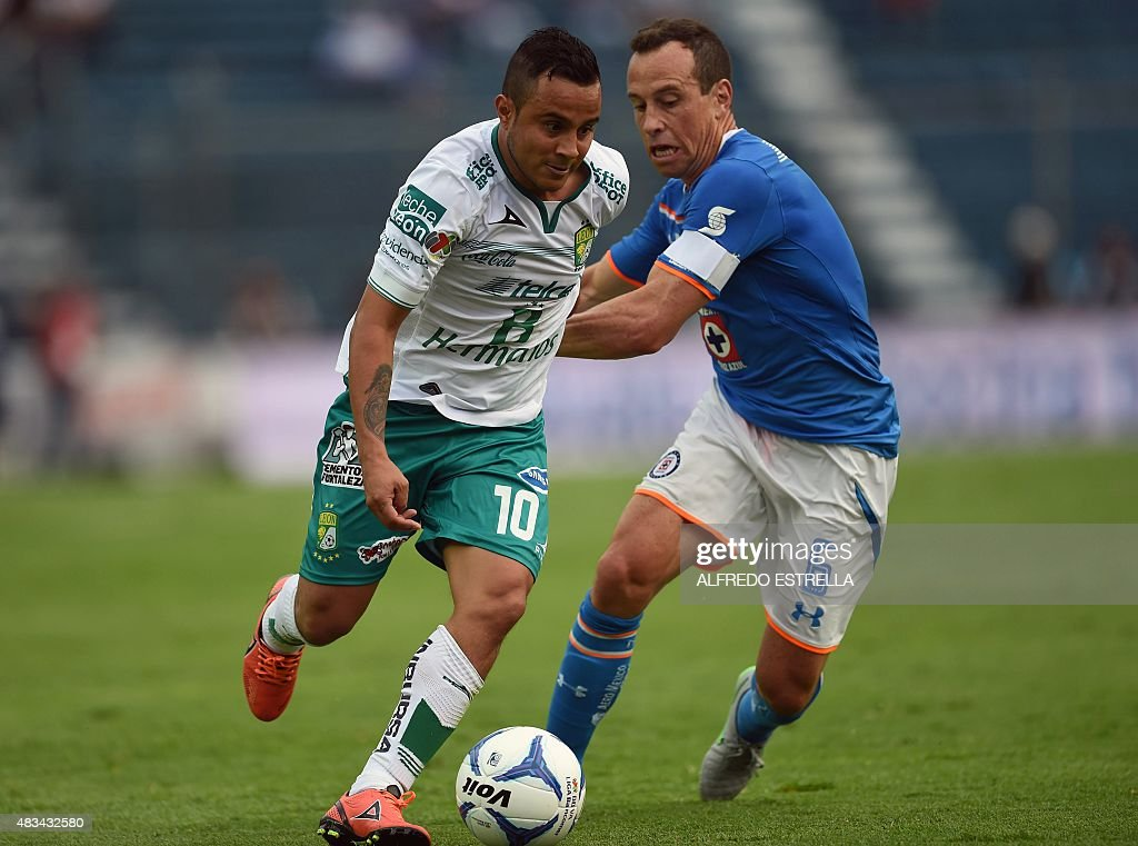 Gerardo Torrado of Cruz Azul vies for the ball with Luis Montes of Leon during their Mexican Football League Apertura Tournament 2015 at the Estadio...