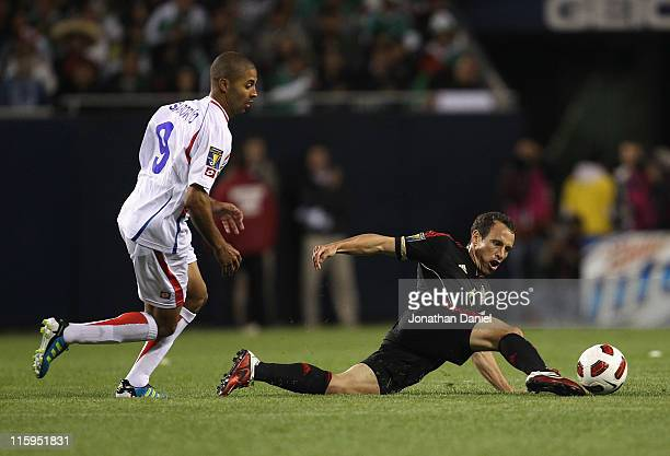 Gerardo Torrado of Mexico dives to the ground to pass the ball under pressure from Alvaro Saborio of Costa Rica during a CONCACAF Gold Cup 2011 match...