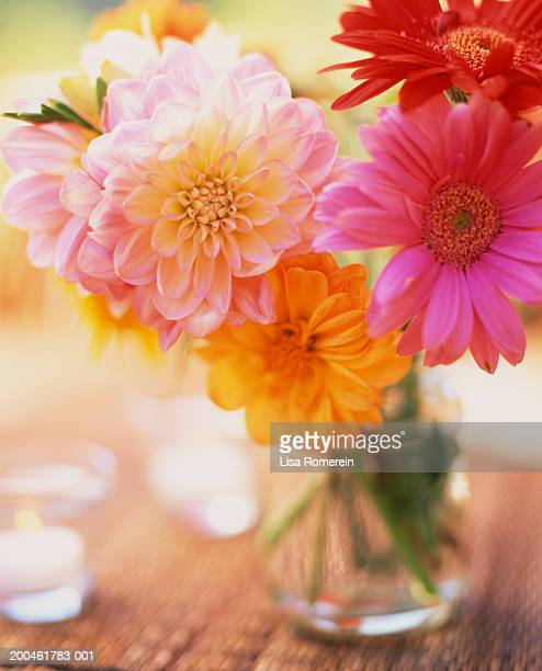 Gerber daisies in vase and candles on table