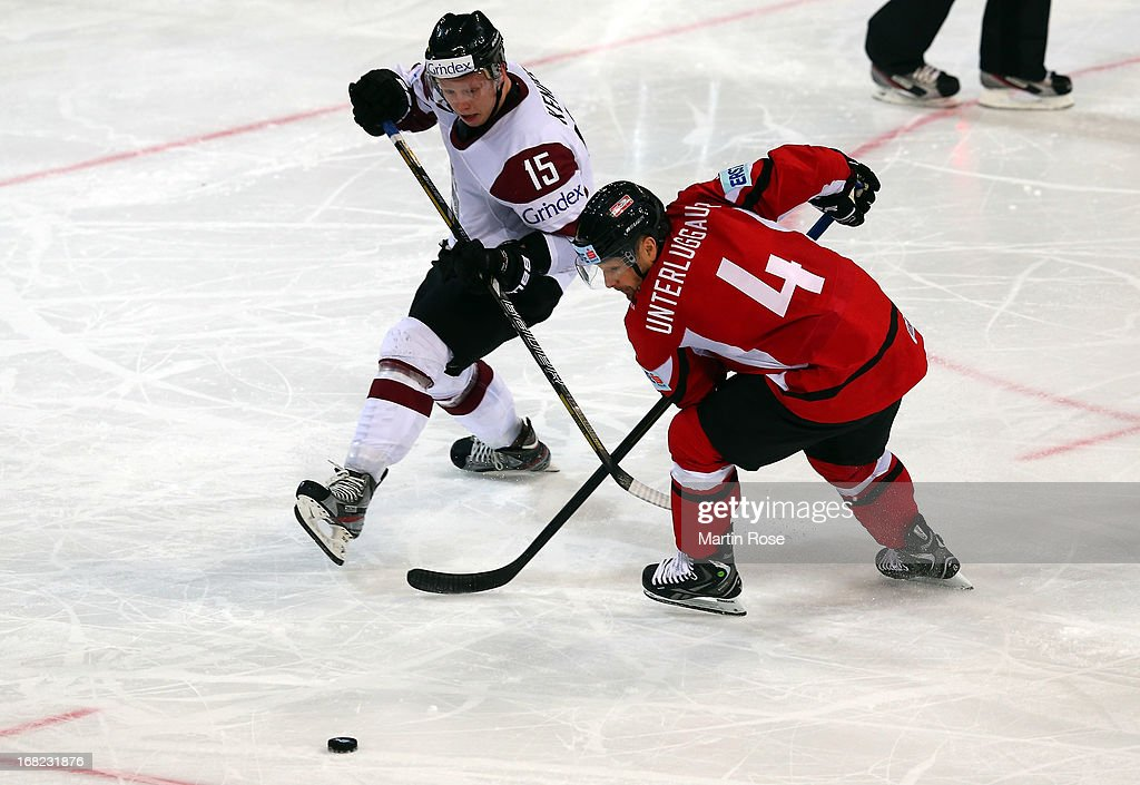 Gerhard Unterluggauer (R) of Austria and Ronalds Kennis (L) of Latvia battle for the puck during the IIHF World Championship group H match between Austria and Latvia at Hartwall Areena on May 7, 2013 in Helsinki, Finland.