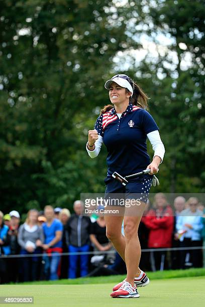 Gerina Piller of the United States holes a par putt on the 18th green to win her match by 1 hole against Caroline Masson of the European team during...